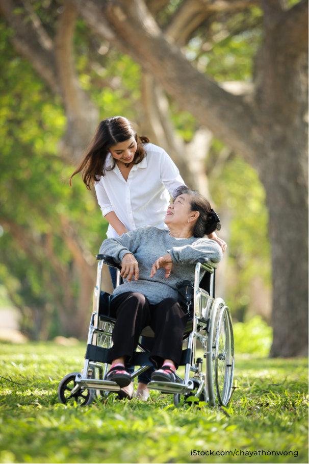 Altenpflegerin schiebt Seniorin im Rollstuhl