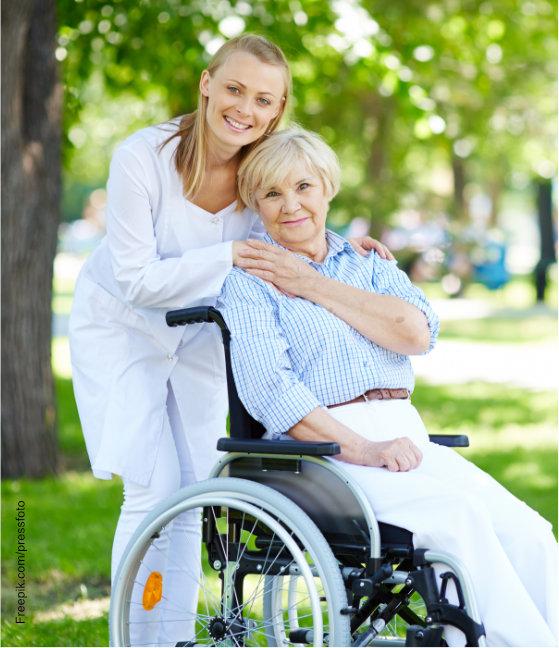 Pflegerin und Seniorin im Rollstuhl