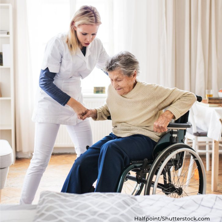 Pflegekraft hilft pflegebedürftiger Seniorin
