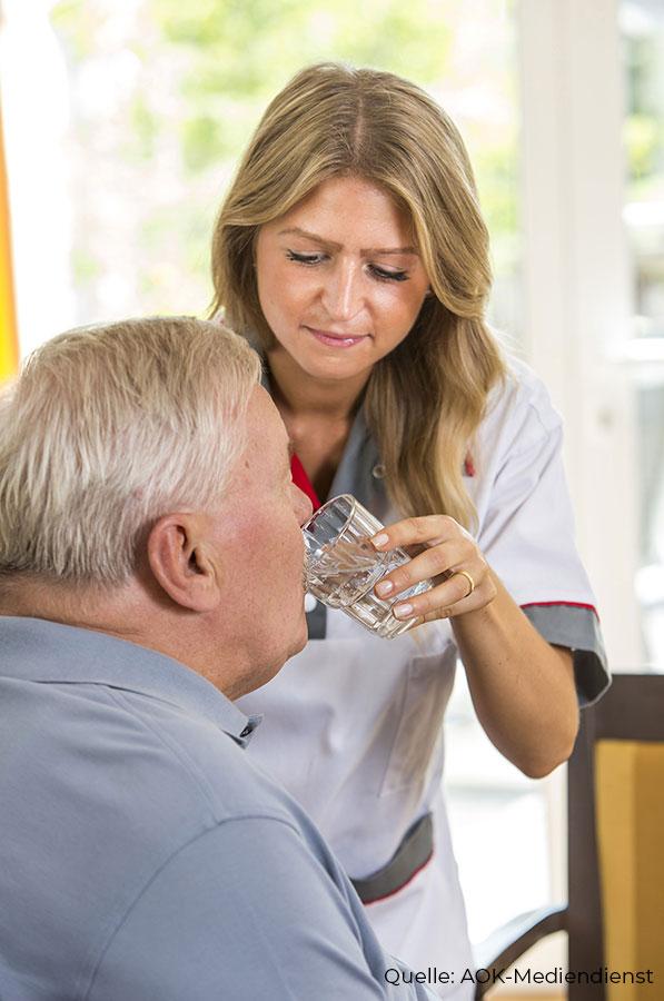 Pflegerin hilft beim Trinken