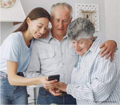 junge Frau hilft Senioren bei Handynutzung