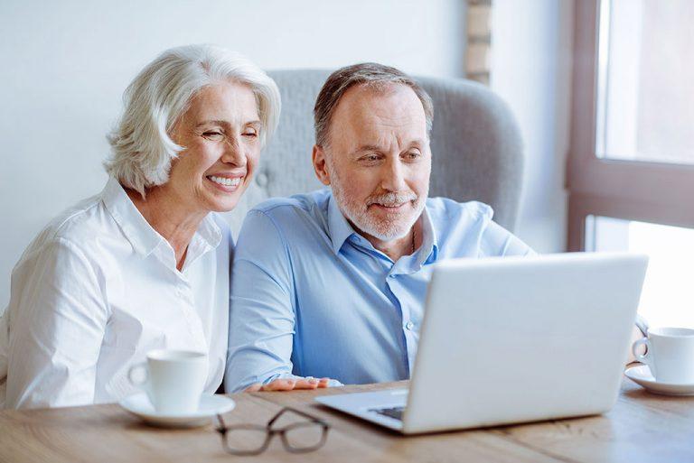 Älteres Paar schaut gemeinsam auf einen Laptop