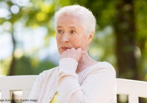old age, retirement and people concept - sad senior woman sitting on bench at summer park