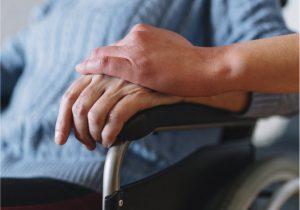 Frau im Rollstuhl mit Pflegeperson