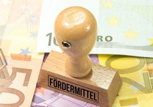 Euro Geldscheine und ein Stempel mit dem Aufdruck Fördermittel