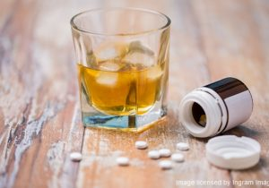 drug abuse, addiction and suicide concept - glass of alcohol and pills on table