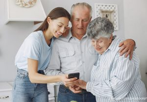 junge Frau (Enkelin) hilft älterem Paar